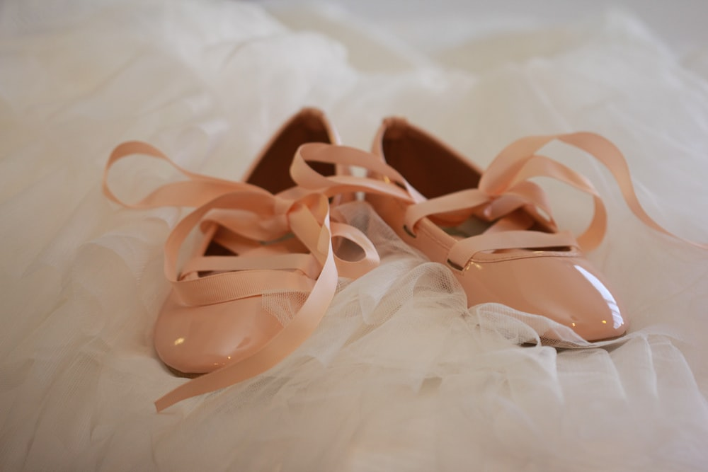 women's beige patent leather shoes on white textile