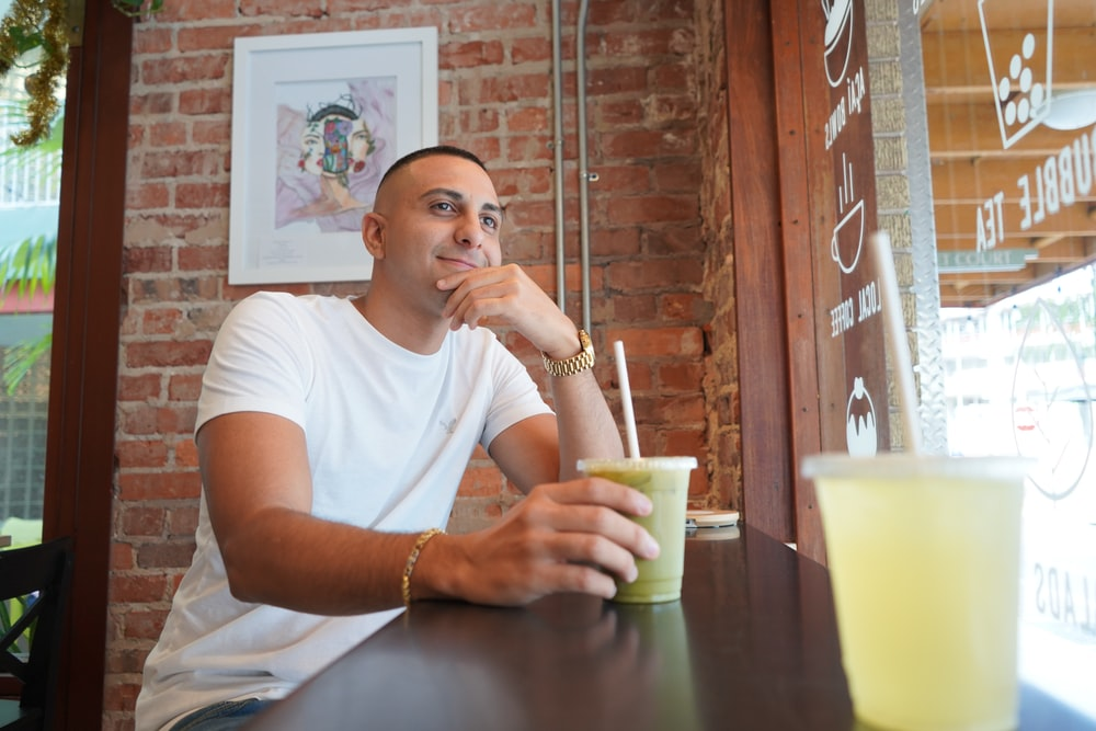 selective focus photography of man sitting on chair wearing white crew-neck t-shirt holding disposable cup filled with cold-served drink