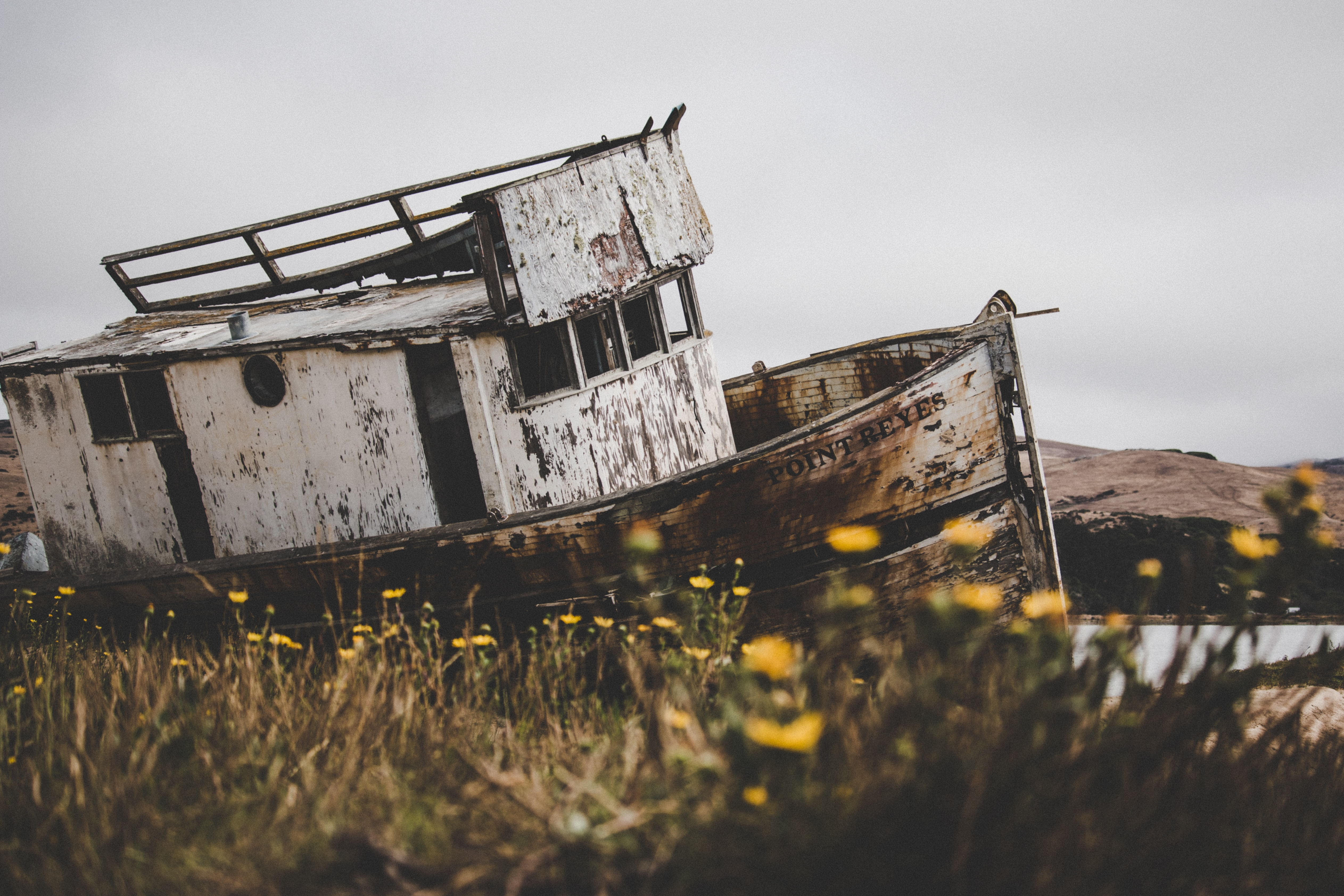 selective focus photography of abandoned tugboat on body of water during daytime