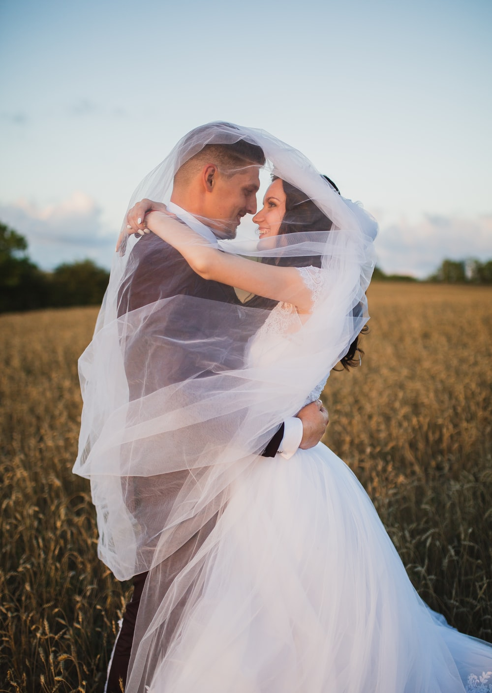 smiling newly wed couple about to kiss in green field