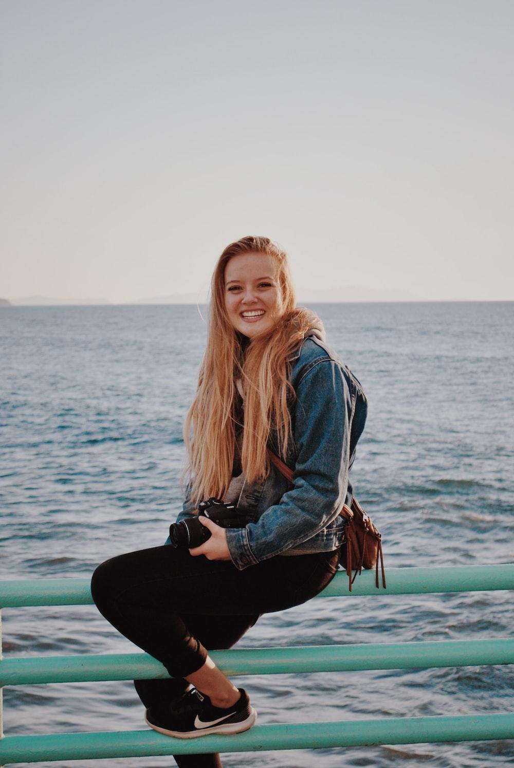 smiling woman sitting on green railings