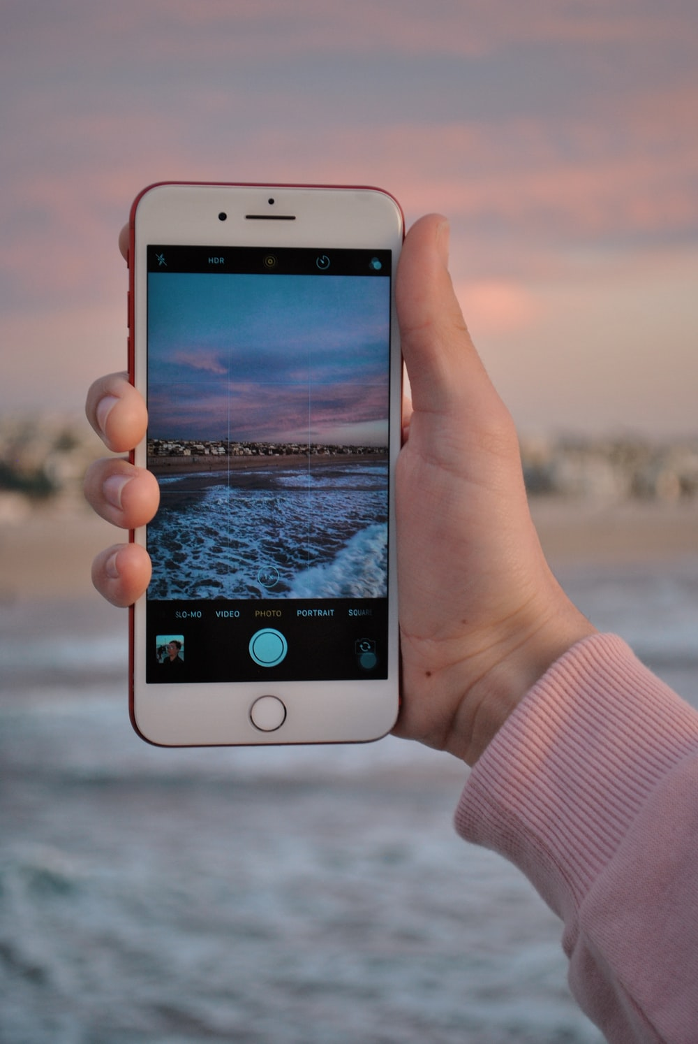 Person Using Product Red Iphone 7 With Seashore Wallpaper Photo Free Cell Phone Image On Unsplash