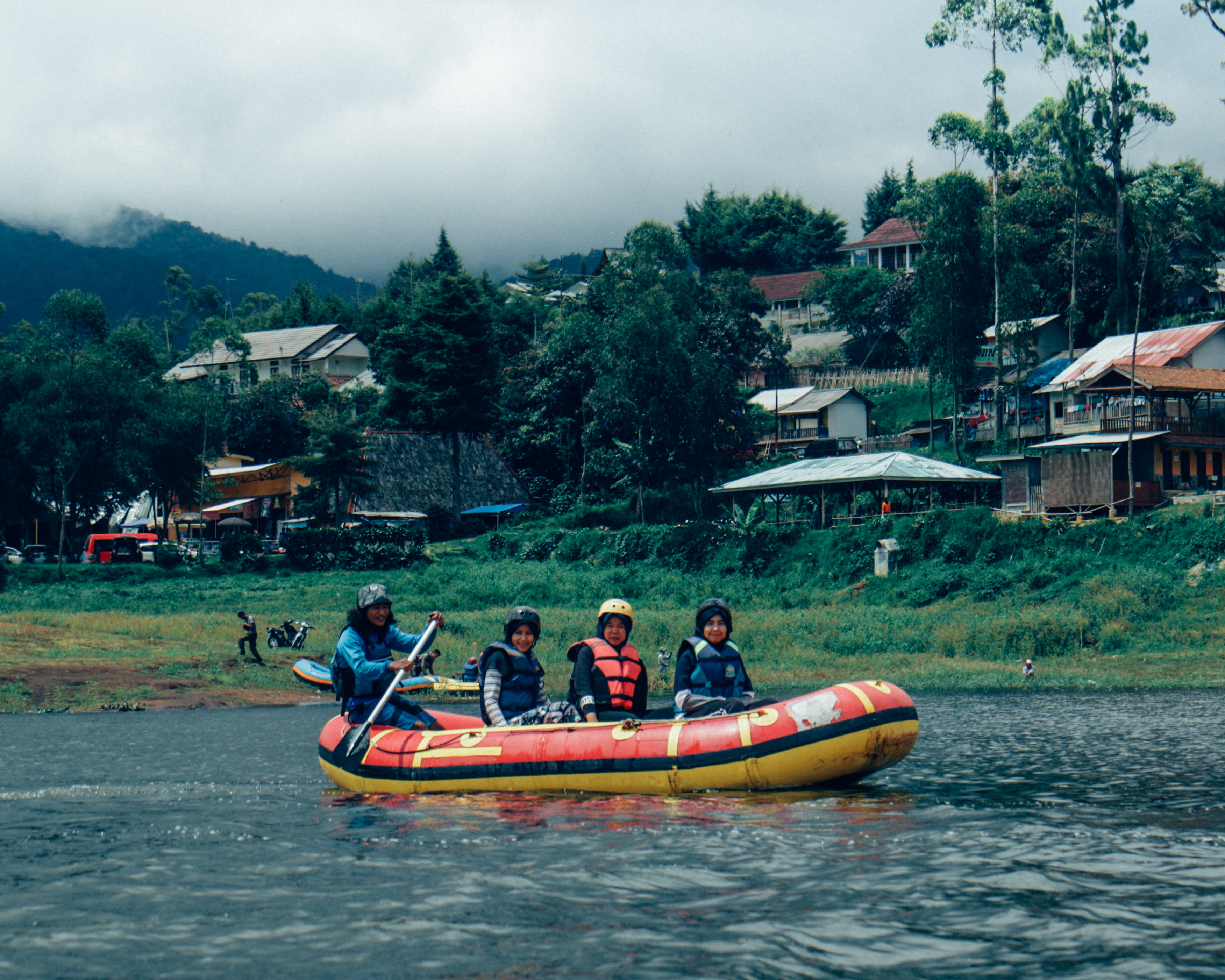 four people riding on inflatable raft boat