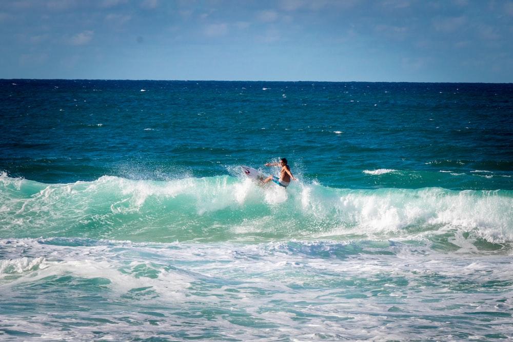 person riding surfboard facing ocean waves