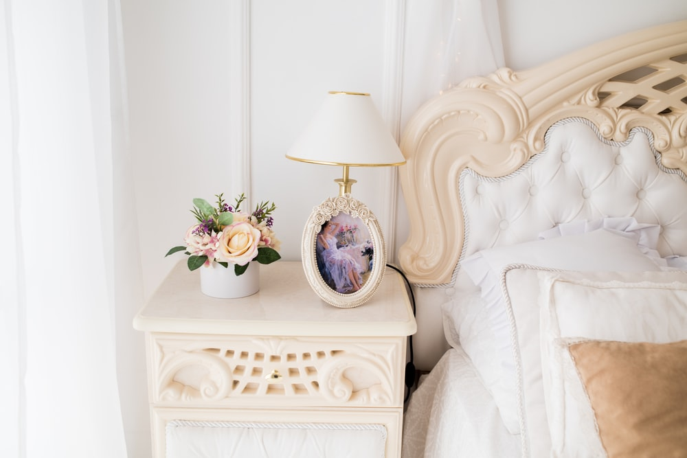 white table lamp on top of white nightstand