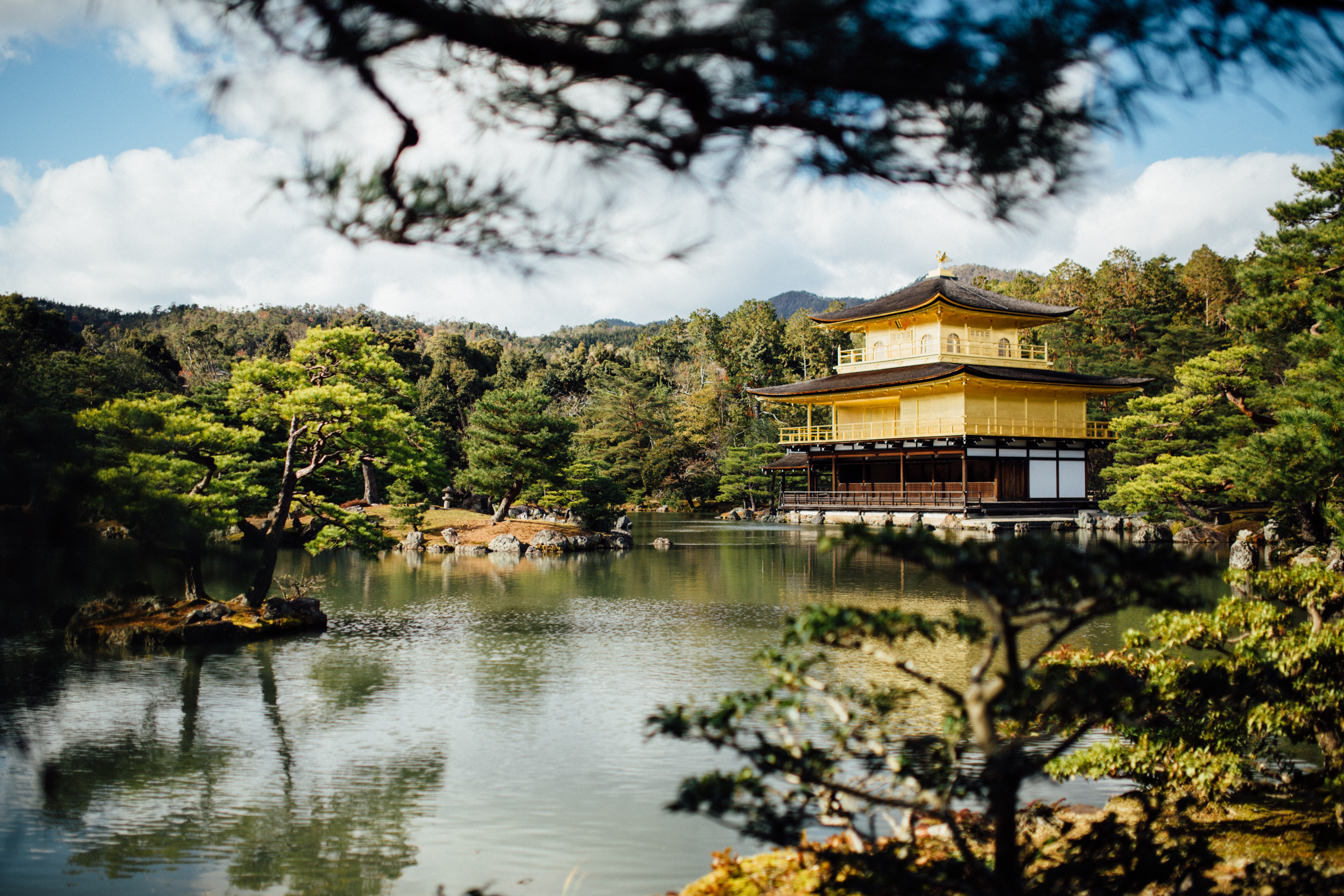 yellow building near body of water and tress