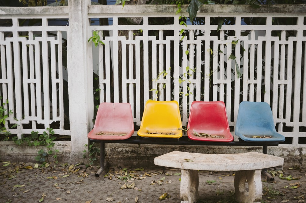 blue, red, yellow, and pink bench near white steel fence