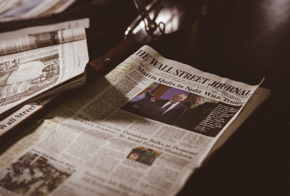 newspaper on black wooden table