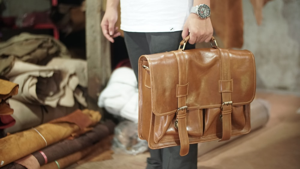 person carrying brown leather handbag
