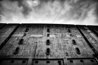 low angle grayscale photo of building under cloudy sky
