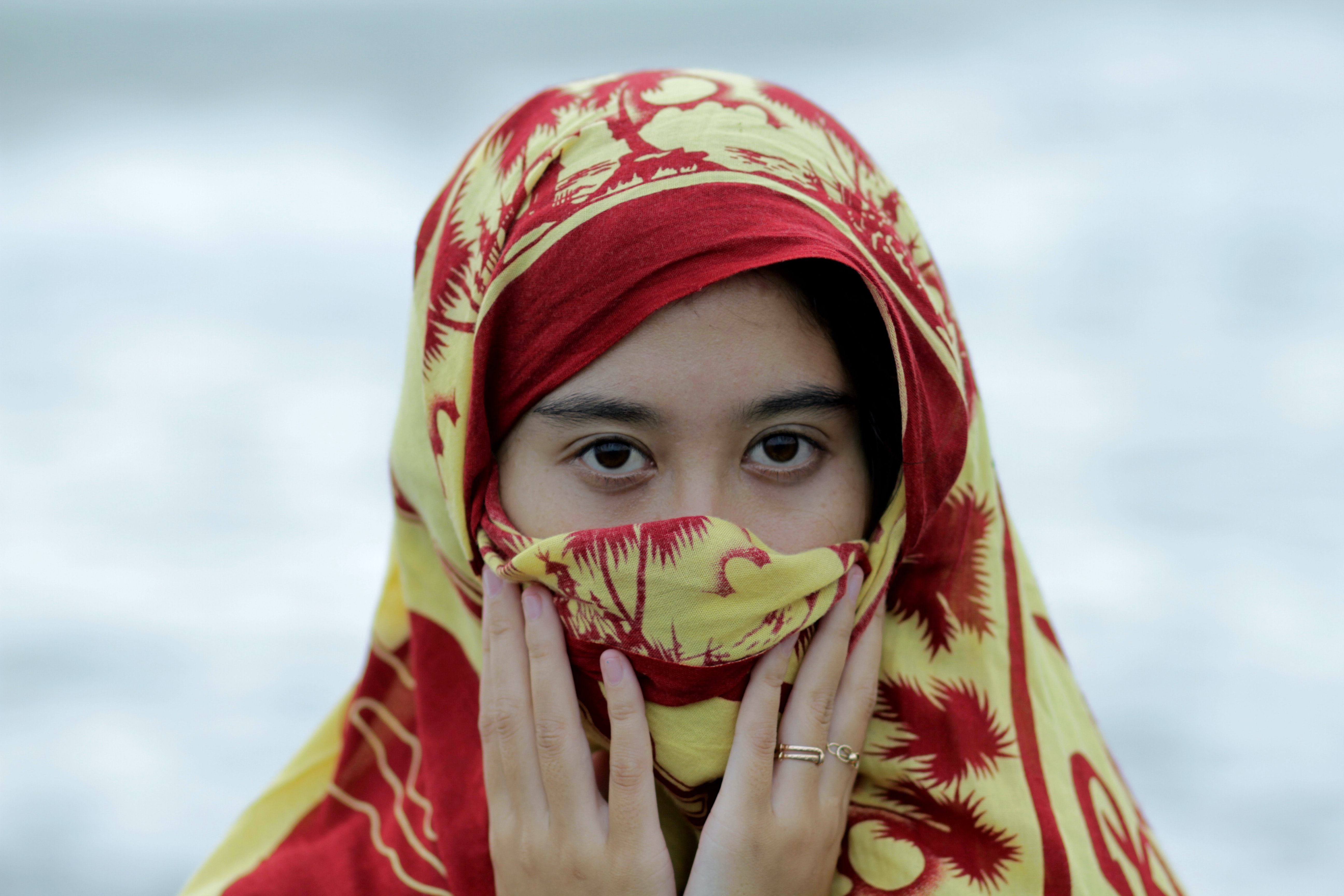 shallow focus photography of woman wearing red and yellow hijab headdress