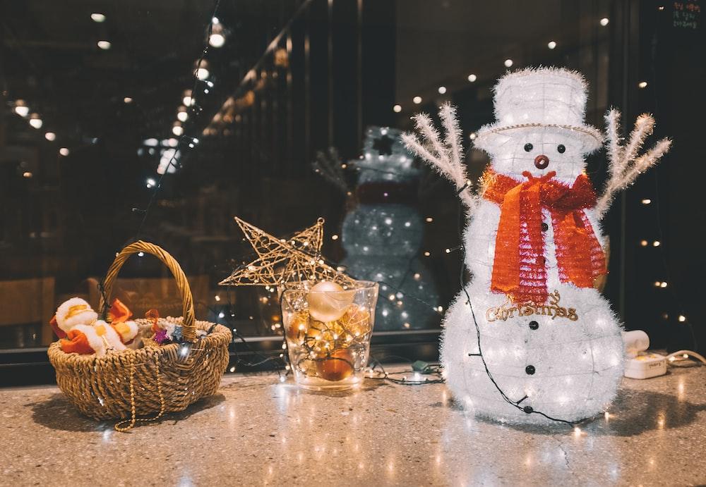 wicker basket, drinking glass, and snowman figurine