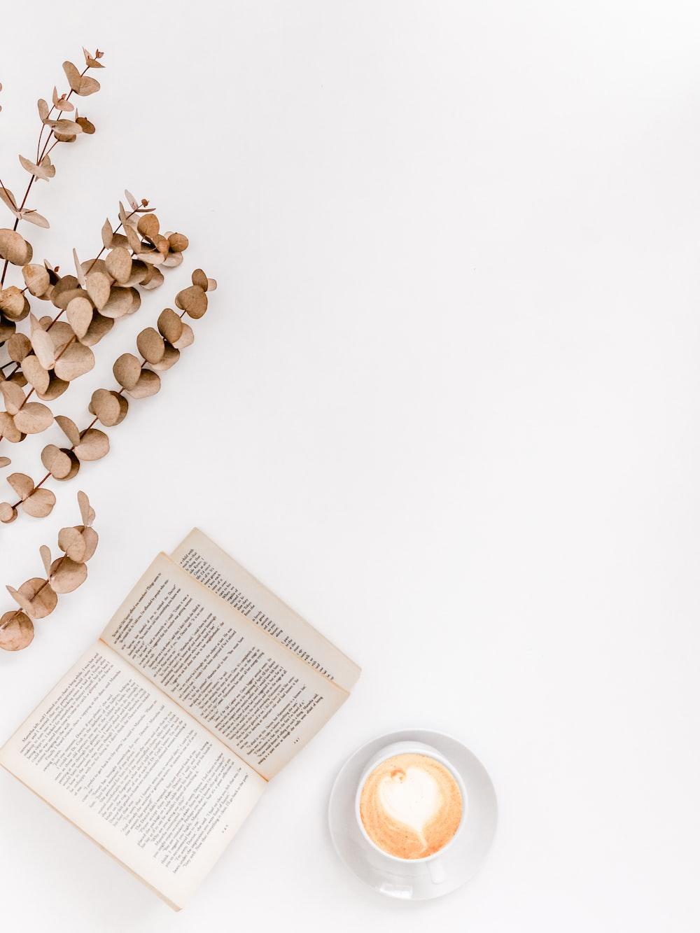 white ceramic mug beside white book