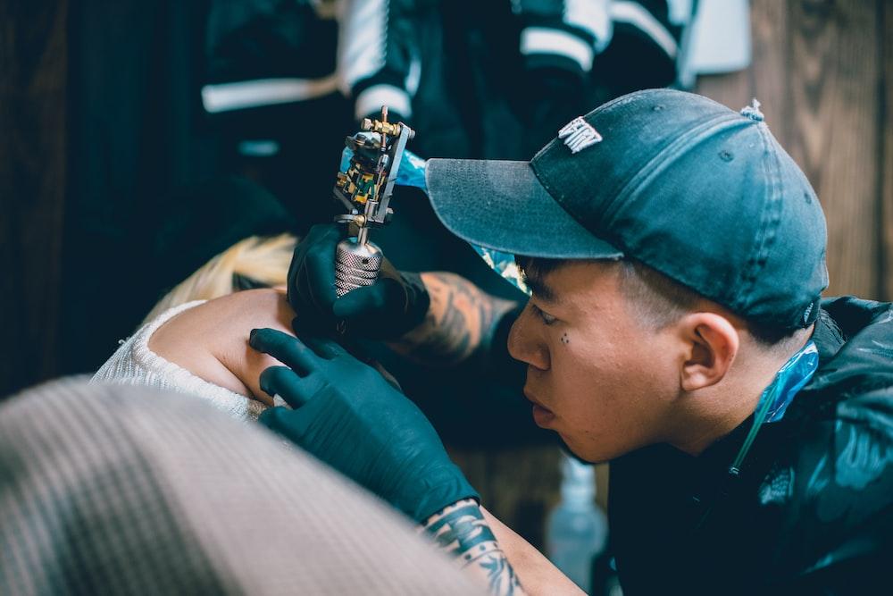 man holding gray rotary tattoo machine making tattoo on person arm
