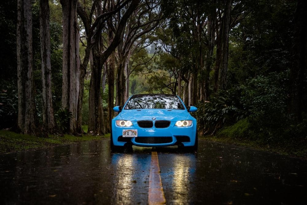 blue BMW car passing through forest