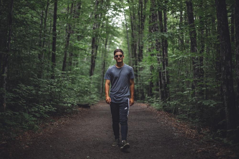man walking under forest
