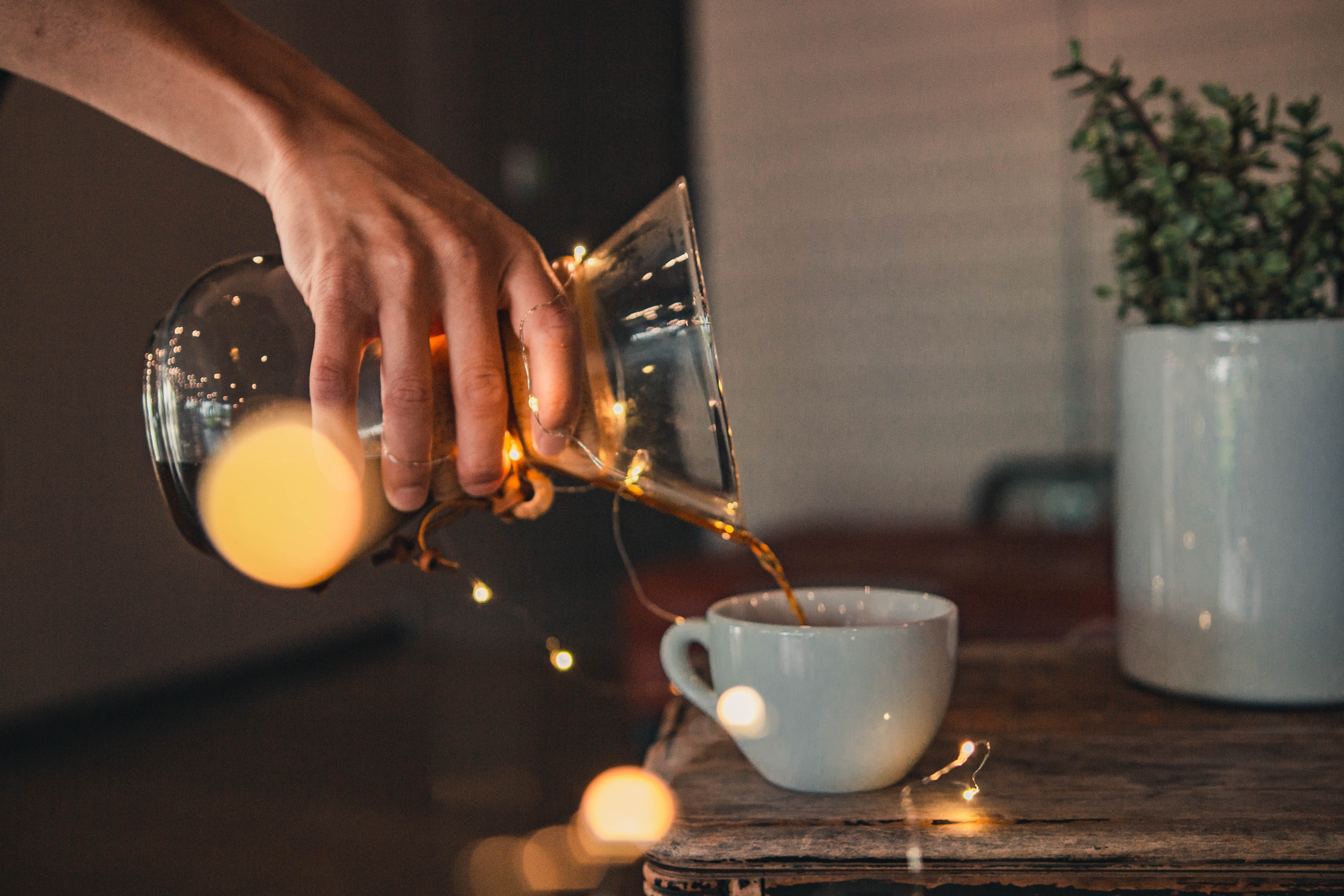 person pouring coffee on white teacup