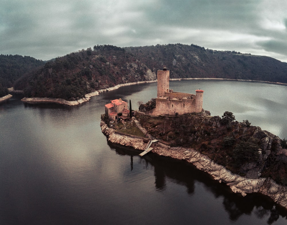aerial photography of brown house beside body of water