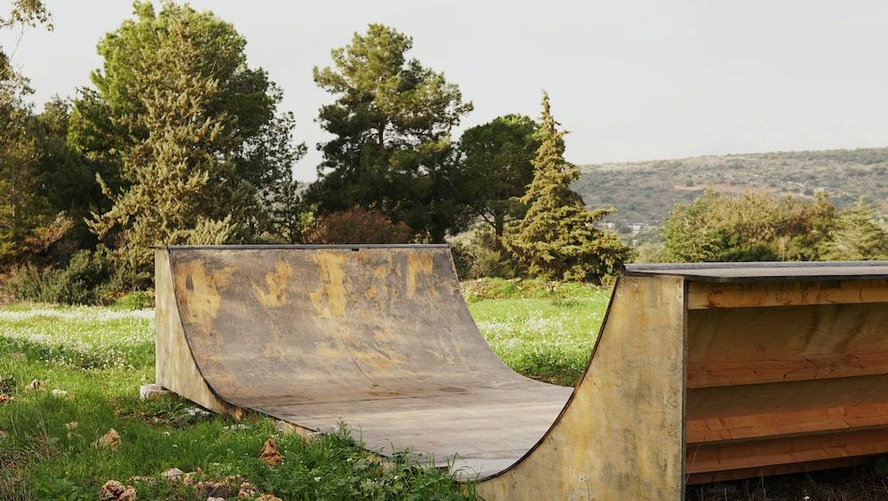 brown wooden skate ramp near green leaf trees