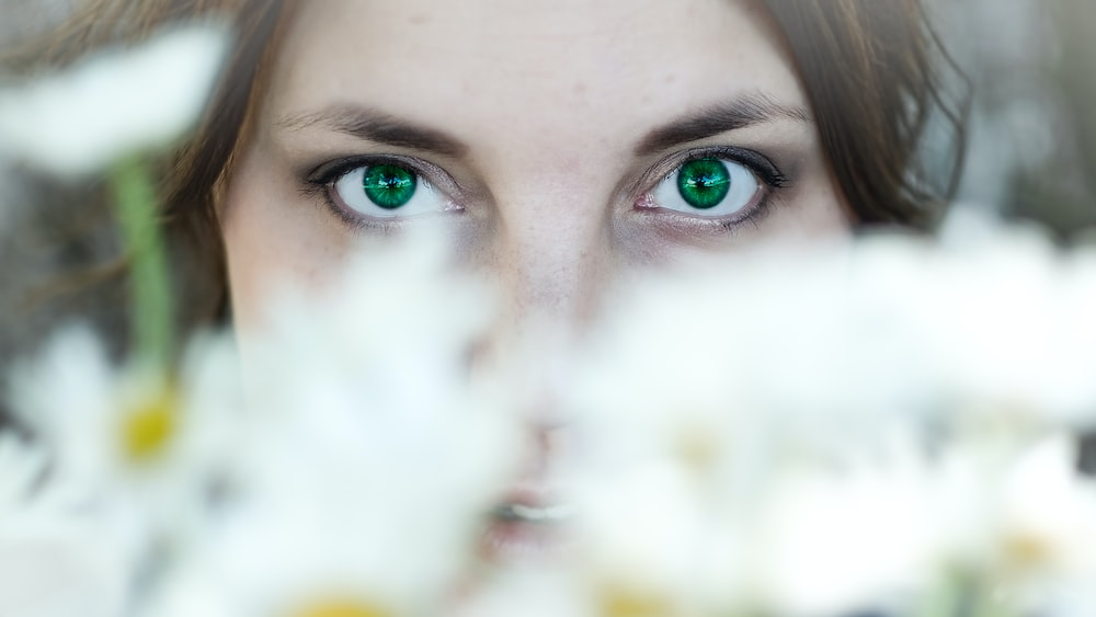 woman's face behind flowers