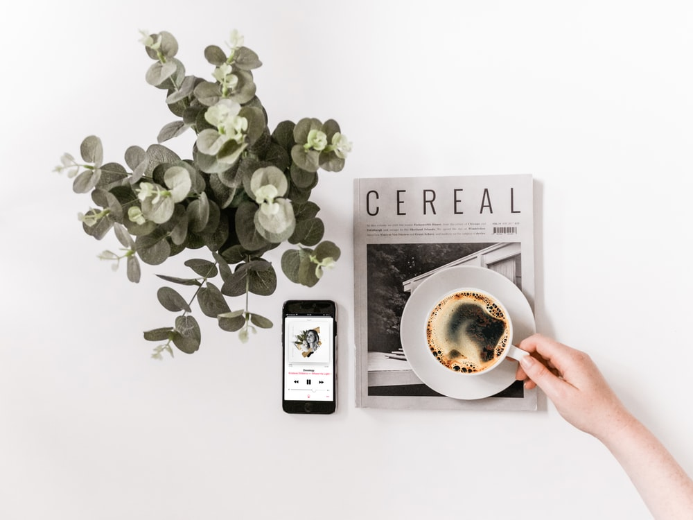 flat lay photography of smartphone, newspaper, and teacup