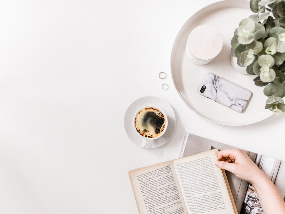 flat-lay photography of person holding opened book on tabletop beside cup of black coffee