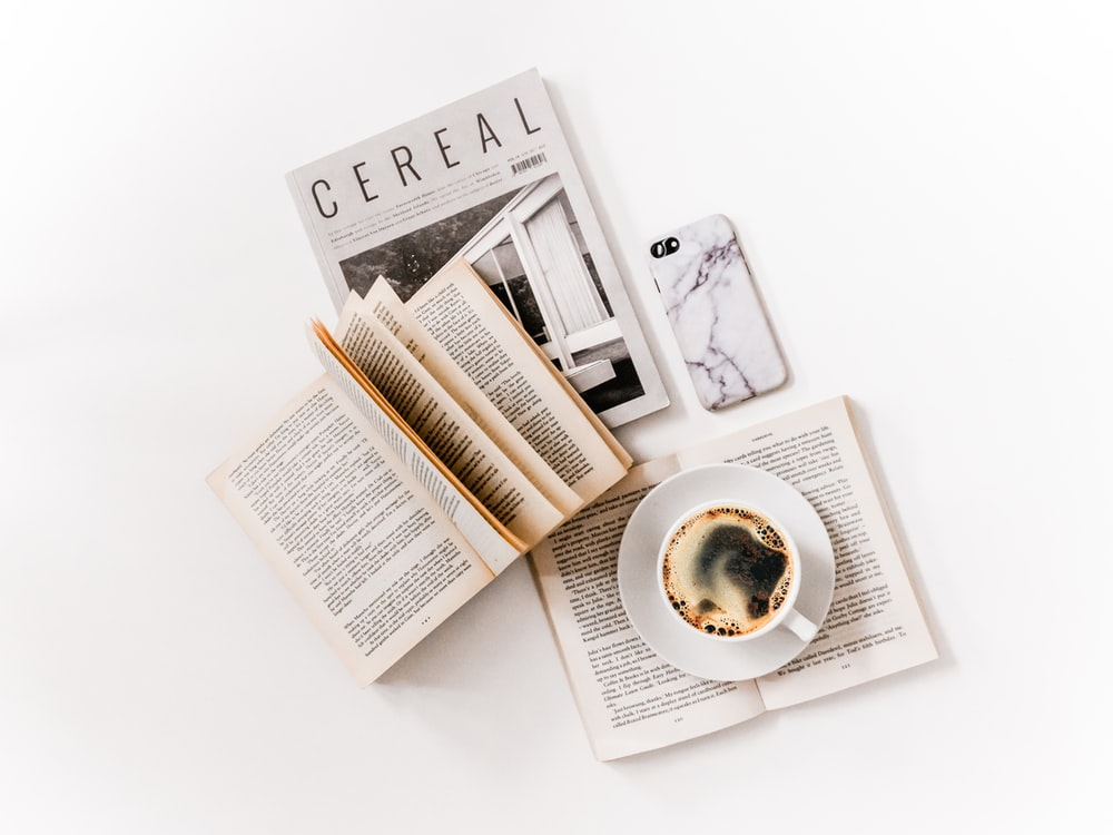 white ceramic cup with coffee on saucer beside opened books