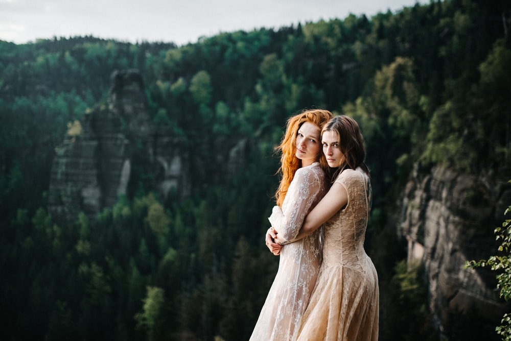 woman hugging woman at her back near trees during day