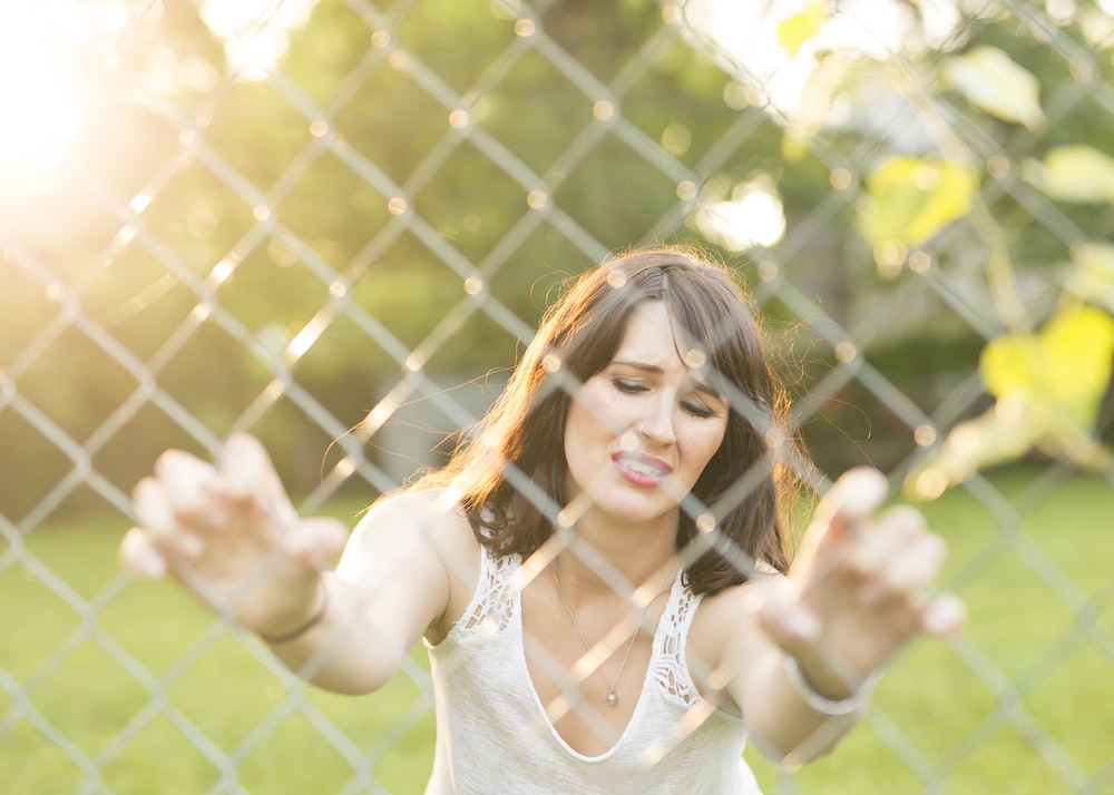 woman closing her eye while holding chain link fence outdoors