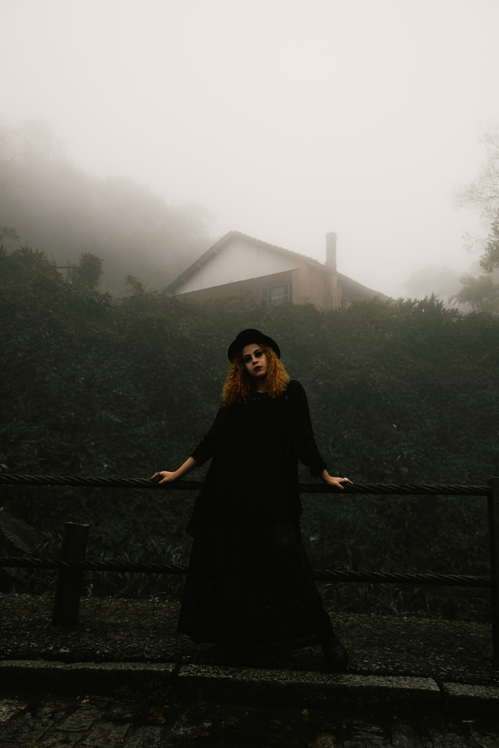 woman in black dress and hat leaning on railings