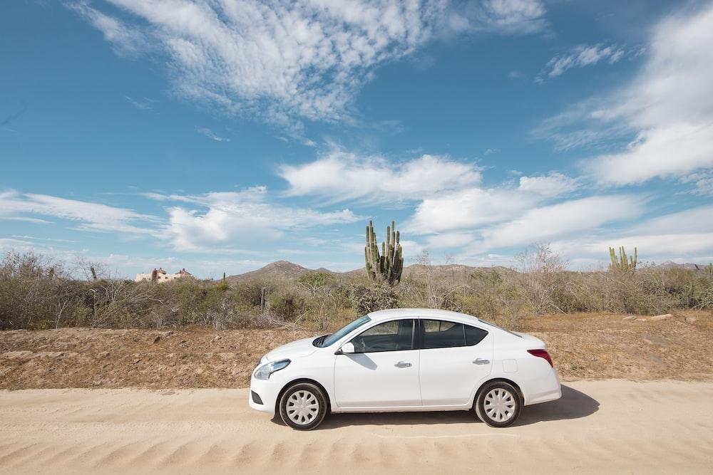 white sedan on sand during daytime