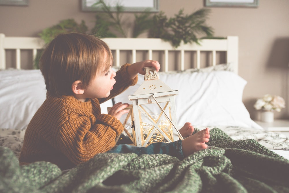 toddler holding candle lantern while sitting on bed