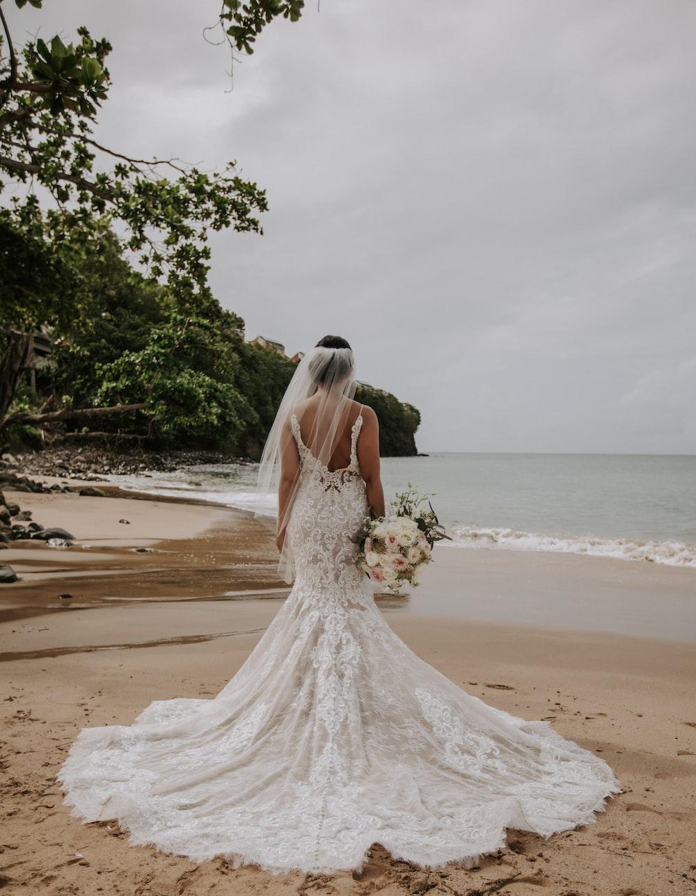 woman wearing wedding dress standing near shore