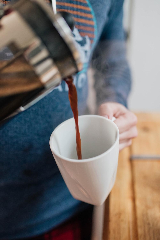 person pouring coffee on white mug