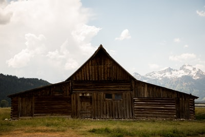 brown wooden barn on field wyoming teams background