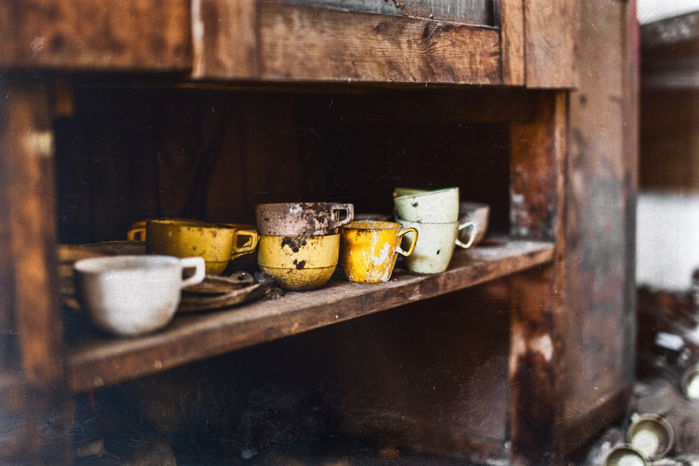 assorted-color teacups on brown wooden shelf