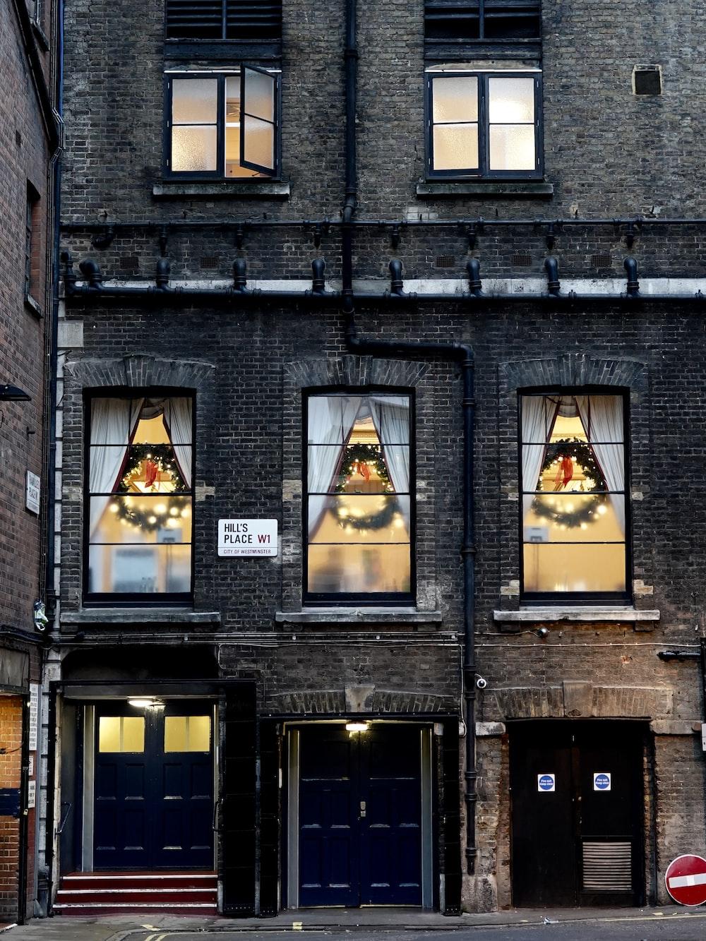 three green Christmas wreaths behind glass windows