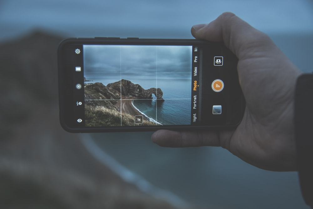 person taking photo of islet