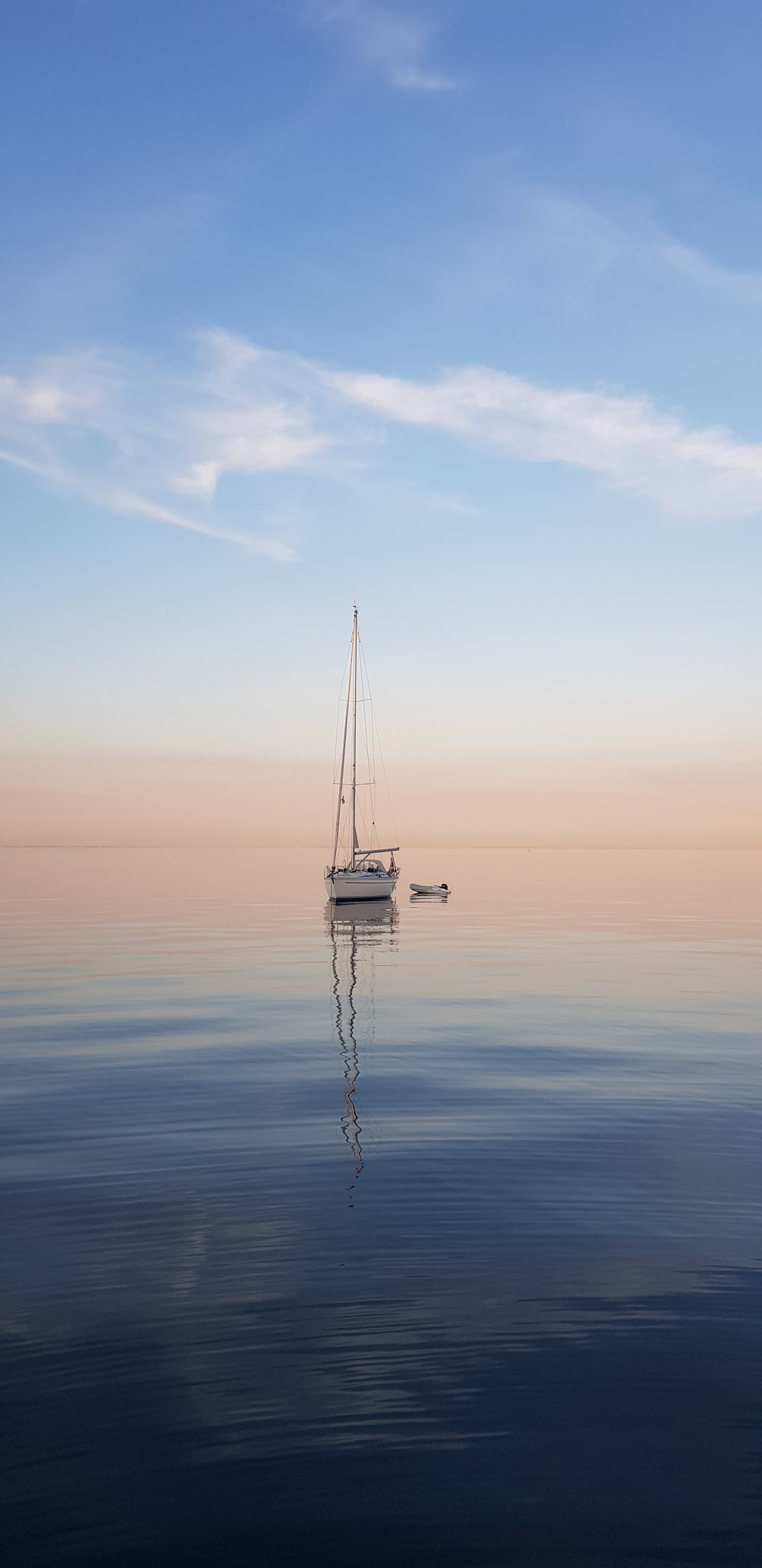 white sailboat at middle of sea