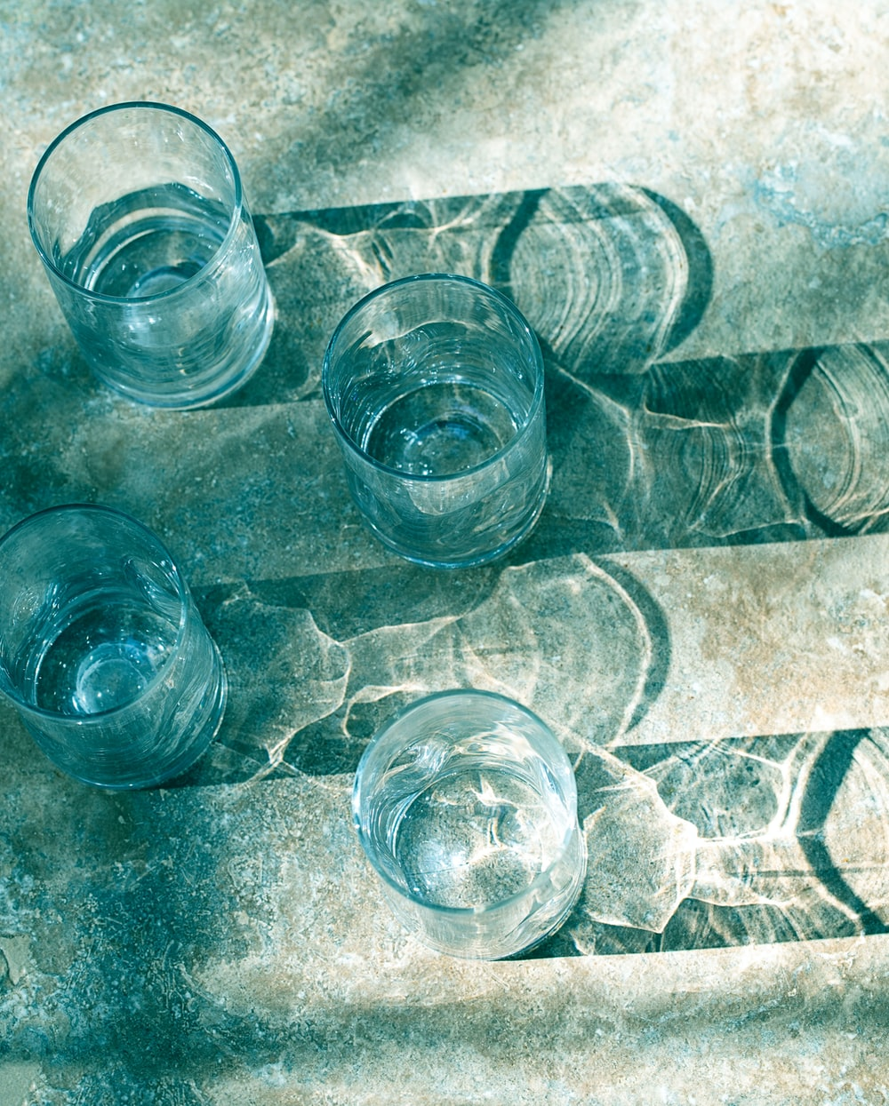 four clear drinking glasses