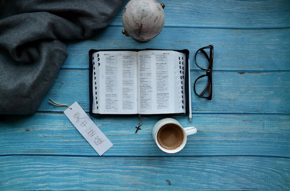 open book beside eyeglasses and mug