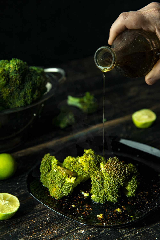 person pouring cola on broccoli