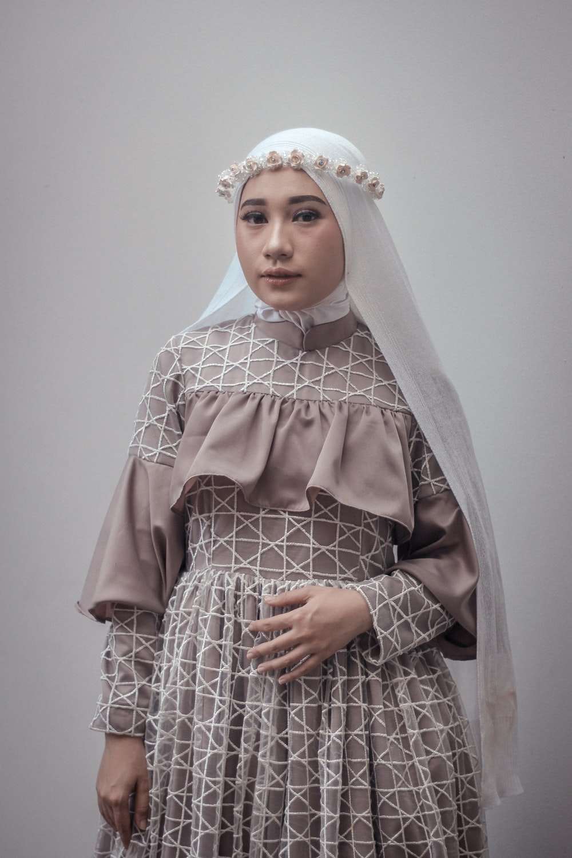 woman in gray abaya standing beside wall