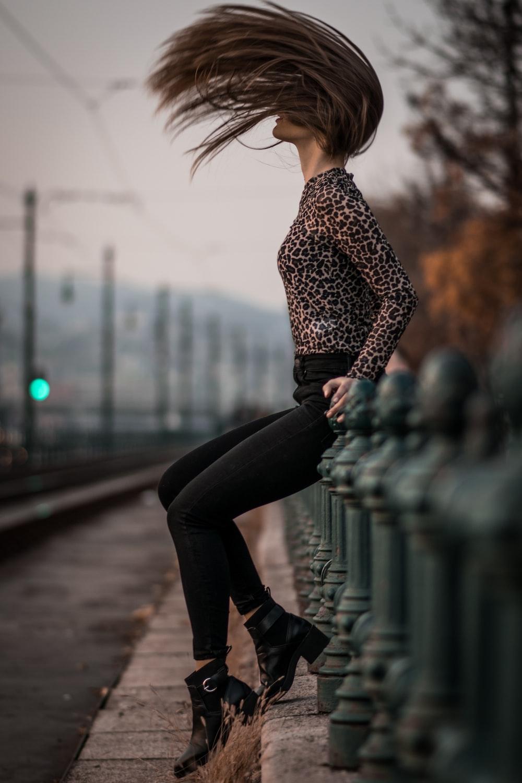 woman sitting while flipping hair during daytime