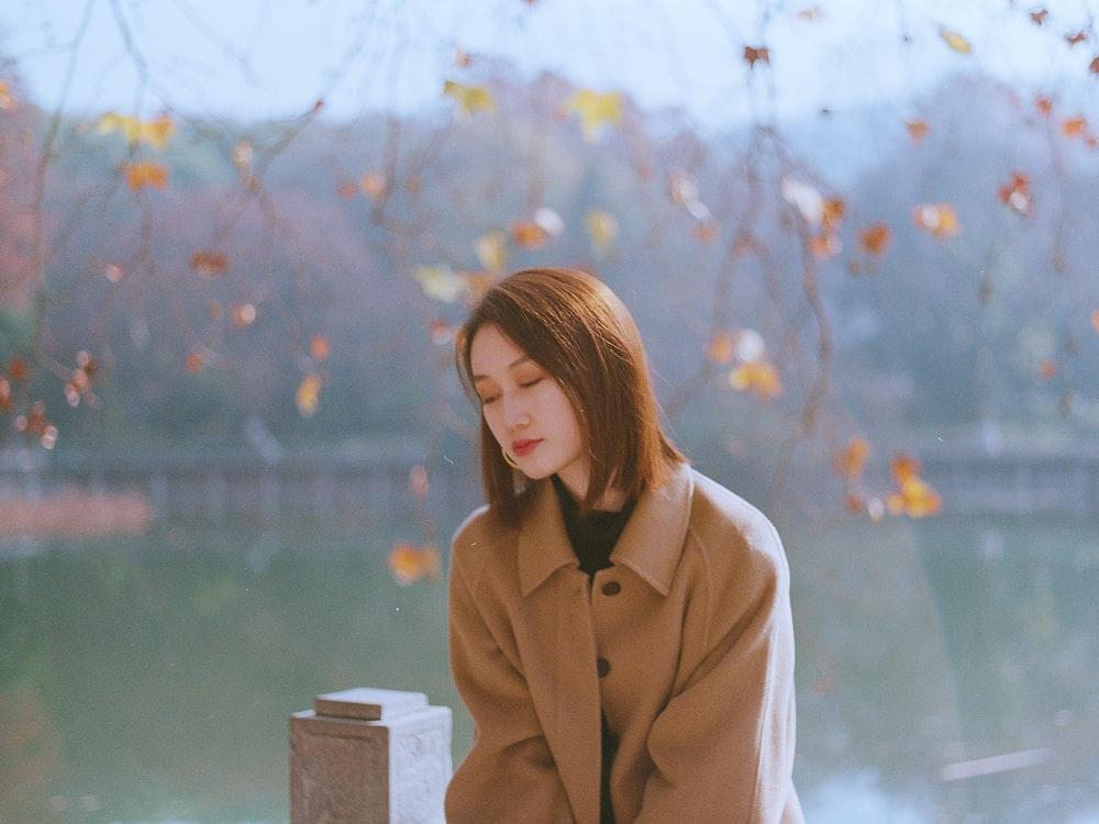 woman in brown coat near body of water