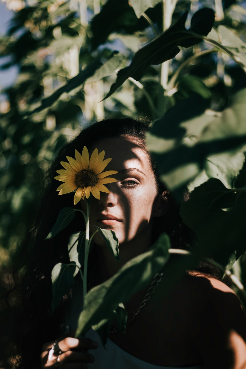 woman covering her right eye with Sunflower