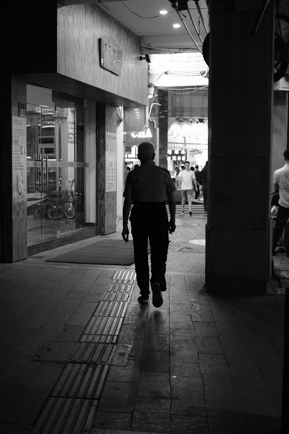grayscale photo of a person walking