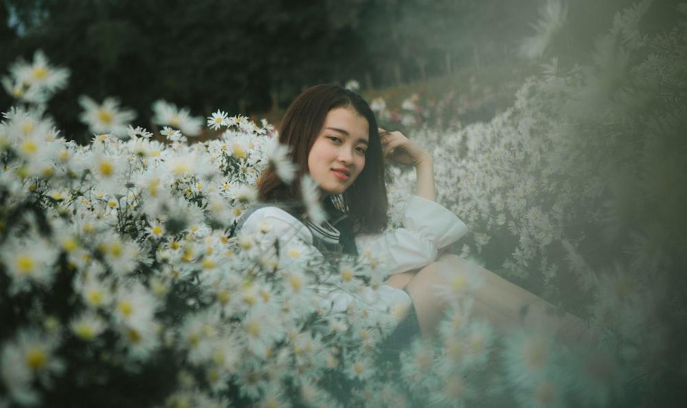 woman sitting on flowers field