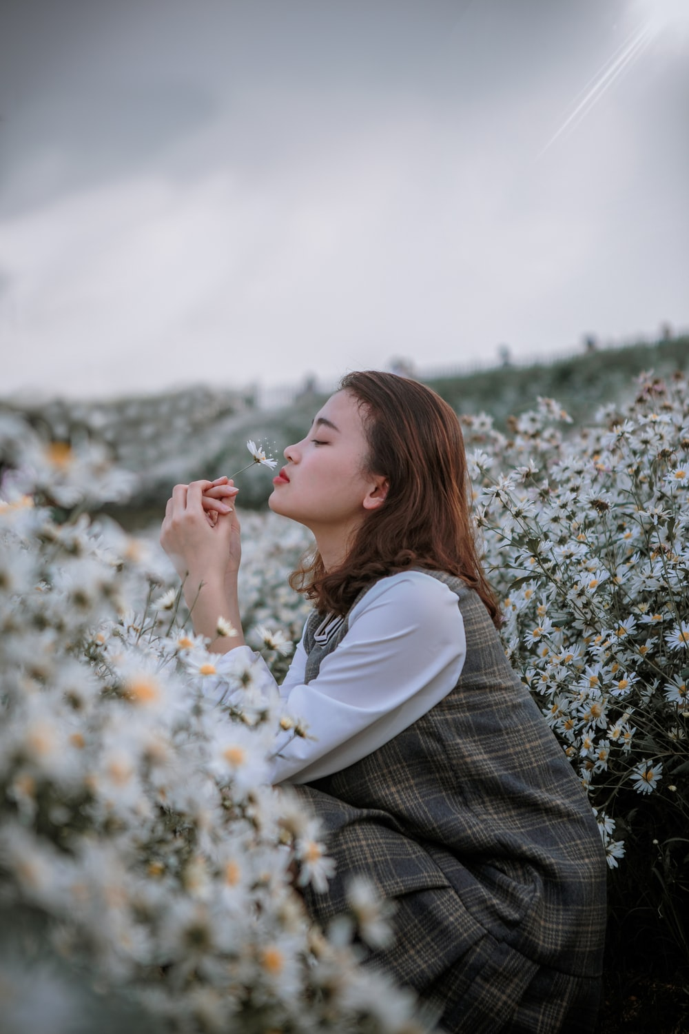 selective focus photography of woman smelling flower