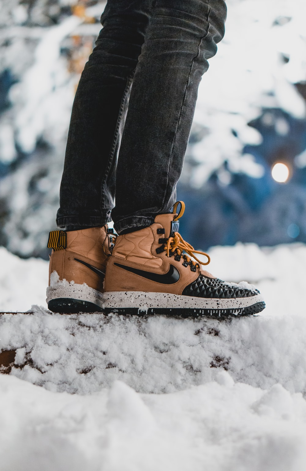 person wearing brown-and-black Nike leather sneakers